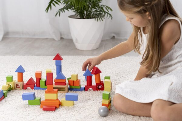 non-binary-kid-playing-with-colorful-game-home-min